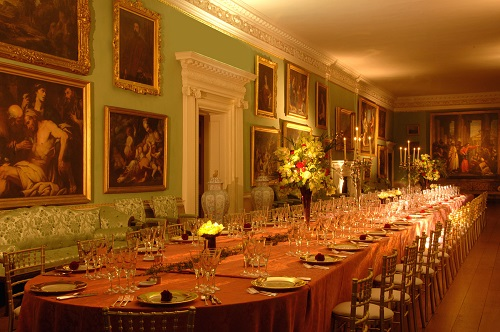 A historic house long gallery with a table set for dinner