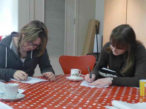 Two women sitting at a table with a red and white spotty table cloth, writing on paper