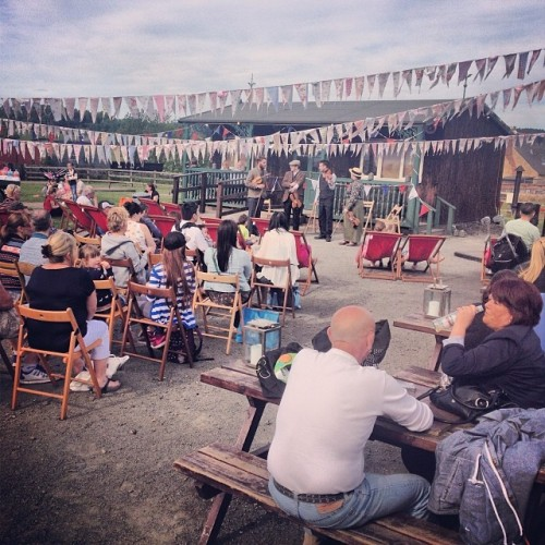 People sitting outdoors under bunting listening to a band