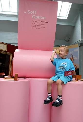 A young visitor sits on some large toilet rolls in Flushed with Pride - you stick your hands in them to find things which have been used as toilet paper over the years.