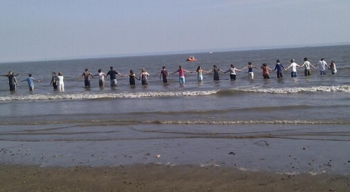 a line of people holding hands in the sea