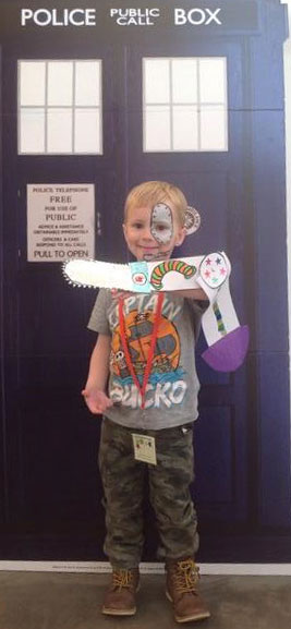 a boy in front of a tardis with a colourful paper arm