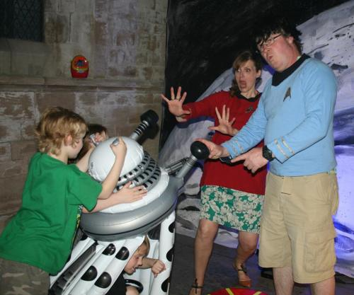 a small boy menaces his parents with a dalek