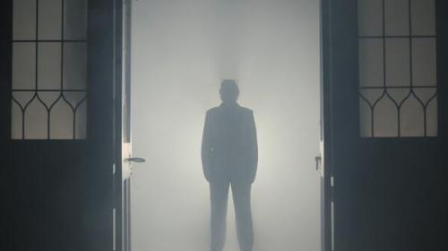 The silhouette of a figure in a suit standing in a doorway in a cloud of dry ice