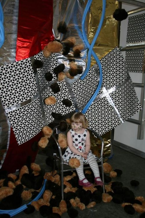 A girl surrounded by small fluffy objects