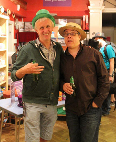 Two men wearing fancy hats and drinking beer in a museum after hours