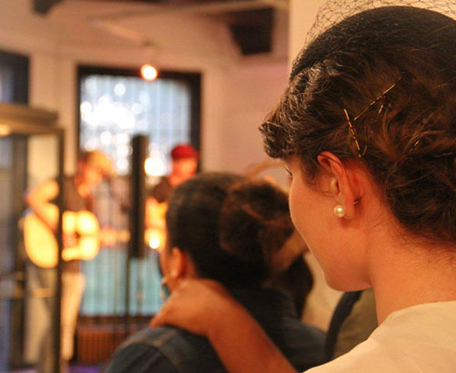 a shot from behind showing the heads of audience members watching a band perform