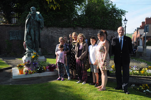 A group of people by a statue with flowers at its feet