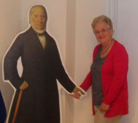 A woman in a red cardigan shaking hands with a cardboard Robert Owen