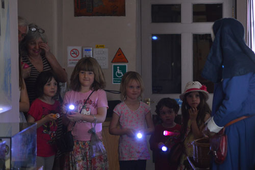 A group of children shining torches in a dark museum