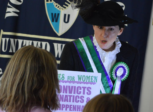 A suffragette and banner