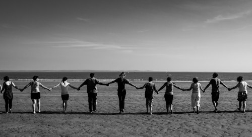 A black and white photo of people on a beach holding hands to walk into the sea