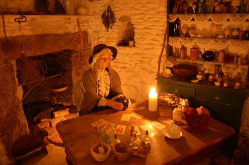 A witch in a candlelit room