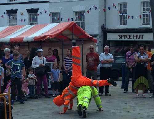 The fluorescent outfits of the breakdancing binmen shine brightly as evening falls