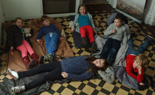 A group of children lying on a museum floor with sleeping bags and torches