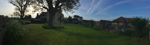 A panoramic photo of a country house in beautiful grounds at dusk