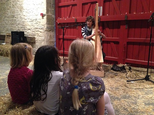 A woman playing a harp in a barn for three children